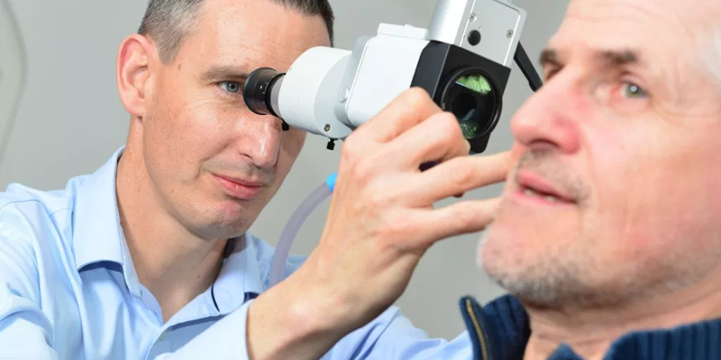audiologist looking into a man's ear