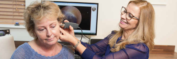 woman getting her hearing tested by a female audiologist